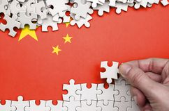 China flag is depicted on a table on which the human hand folds a puzzle of white color.  stock photos
