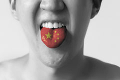 China flag painted in tongue of a man - indicating Chinese language and speaking in Black and White tone. Stock Image