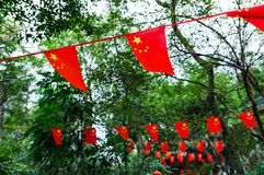 China flag. Peoples Republic of China flags waving against green trees.  stock photos
