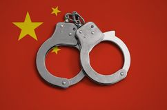 China flag and police handcuffs. The concept of observance of the law in the country and protection from crime.  stock photos