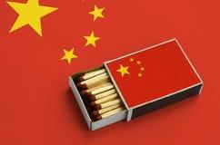 China-Flagge wird in einer offenen Streichholzschachtel gezeigt, die mit Match gefüllt wird und auf einer großen Flagge liegt lizenzfreies stockfoto