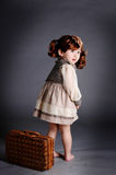 China girl of 1920s with lugga. The girl wearing 1920s clothes and carrying the luggage of the 1920s.A view of the baby·s back Stock Image