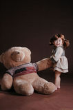 China girl draw the teddy bear. The girl wearing 1920s clothes and draw the big teddy bear who wear the US flag clothes Royalty Free Stock Photography