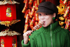 China girl eating candied fruit Stock Images