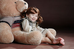 China girl in the teddy bear's arm. The China girl wearing 1920s clothes and in the big teddy bear's arm who wear the US flag clothes Royalty Free Stock Photos