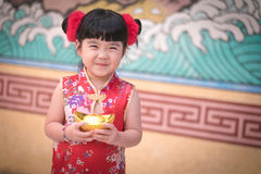 China girl in traditional Chinese dress greeting, holding a gold Royalty Free Stock Images