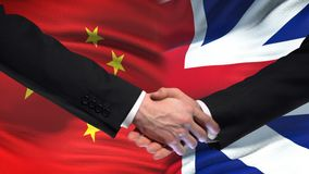 China and Great Britain handshake, international friendship, flag background. Stock footage stock video