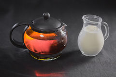 China green blooming tea Bud in a glass teapot. Milk in a small jug on b. Lack background royalty free stock photography