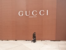 China: Gucci opening soon. CHONGQING, CHINA - JAN 22: three men walk under a Gucci opening soon advertisment in Chongqing on Jan 22, 2011. In 2009, Chinese Royalty Free Stock Photo