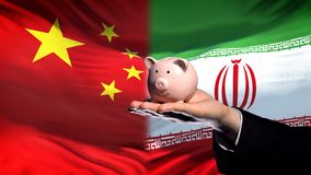 China investment in Iran, businessman hand holding piggybank on flag background. Stock photo royalty free stock photography
