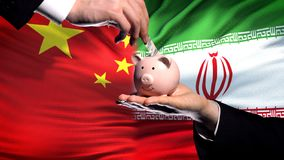 China investment in Iran, hand putting money in piggybank on flag background. Stock photo stock image