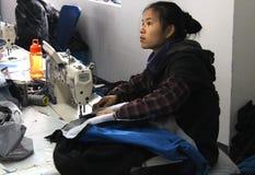CHINA - 15. JANUAR: Junge Näherin auf Chinesisch kleidet Fabrik stockfotos