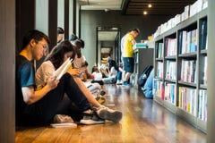CHINA JUNIO DE 2018: Pueblo chino que se sienta en el libro de lectura del piso Foto de archivo libre de regalías