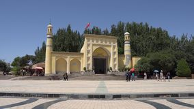 China Kashgar Mosque. Kashgar Id Kah Mosque with a Waving China Flag on the Top of the Roof and Chinese Tourists with Two Walking Police Officers stock video