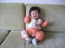 China lovely baby. The baby pull on the China cloths and laugh all day Stock Photo