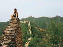 China - Mann, der auf der Chinesischen Mauer sitzt stockfotos