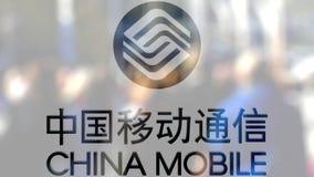 China Mobile-embleem op een glas tegen vage menigte op steet Het redactie 3D teruggeven Stock Fotografie