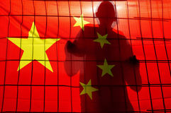 China national flag. BEIJING - APR 24:Silhouette of Chinese behind fence and China flag on April 24 2009.There are about 1.5 million people in prison in China stock image