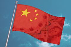 China national flag overlaid with Yuan renminbi banknotes waves on blue sky background. Chinese money and political situation.