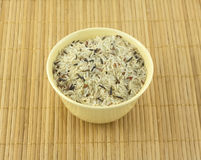 Rice in bowl on mat. China rise in beige bowl on brown straw mat closeup stock photo
