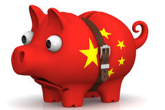 China's economic crisis. Concept. Tightened with a strap pig piggy bank with bulging eyes, in the color of the Chinese flag on a white surface. The concept of Royalty Free Stock Image