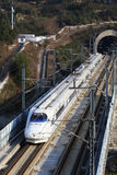 China's High Speed Railway white train wear out from the cave. White high-speed railway locomotive running on the railway tracks a wire Stock Photography