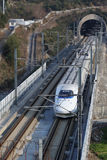 China's High Speed Railway white train wear out from the cave. White high-speed railway locomotive running on the railway tracks a wire Stock Images