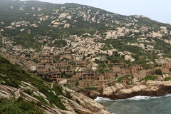 China's most eastern end of the fishing village is called the potala palace in the sea. Weathering of rocks and low vegetation, a curved path through the village royalty free stock image