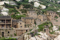 China's most eastern end of the fishing village is called the potala palace in the sea. Weathering of rocks and pieces of green plants, the village house path stock image