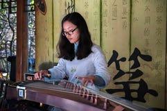 CHINA, SHANGAI - 7 DE NOVIEMBRE DE 2017: La muchacha china está jugando Guzheng o a zheng Los chinos desplumados tocan la cítara  Fotografía de archivo libre de regalías