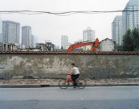 China shanghai bike. Women riding pass building works in shanghai Royalty Free Stock Image