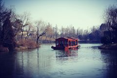 China-style boat at famous Slender West Lake during winter, located at YangZhou, Province JiangSu, China. It is a china-style boat tour to bring tourist cruise Royalty Free Stock Photography