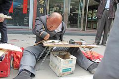 China, Suzhou - April 14, 2012. A man with a disabled person writes calligraphy, Chinese characters on the fan, sneers for. Tourists stock photography