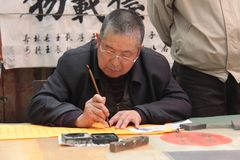China, Suzhou - April 14, 2012. The man writes Chinese characters with a brush, calligraphy in China. The man is Chinese.  royalty free stock photography