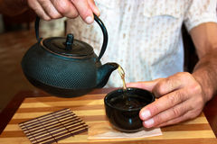 China tea ceremony. Man pours tea into a cup Stock Photos