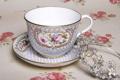China Tea Cup. A china tea cup and tiara on vintage floral background Royalty Free Stock Photography