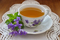 China tea cup with violets Stock Photos