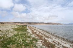 China, Tibet, the sacred lake for Buddhists Manasarovar in june in cloudy weather.  stock photography