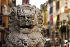 China Town 1. Close up of lion statue in Antwerpens China Town with Chinese stores and advertising signs in the background stock images