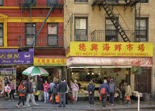 China Town, Manhattan, New York City. People walk and shop the busy retail stores in colorful China Town, lower Manhattan in New York City, looking for fish, and stock photo