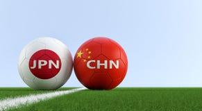 China versus Het Voetbalgelijke van Japan - Voetbalballen in China en de nationale kleuren van Japans op een voetbalgebied Royalty-vrije Stock Afbeelding