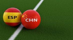 China versus Het Voetbalgelijke van Spanje - Voetbalballen in China en de nationale kleuren van Spains op een voetbalgebied Royalty-vrije Stock Fotografie