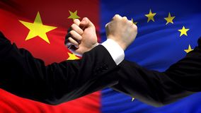 China vs EU confrontation, countries disagreement, fists on flag background. Stock photo stock photos