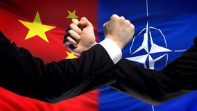 China vs NATO confrontation, countries disagreement, fists on flag background. Stock photo royalty free stock photo