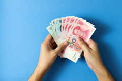 China Yuan currency notes. Hand with China Yuan currency notes over blue background Stock Images