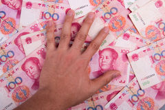 China Yuan. One hand on the China Yuan Royalty Free Stock Image