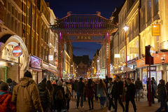 Chinatown at night. LONDON, UK - JANUARY 02: Pedestrians walking through traditional Chinese portal in  Gerrard Street at night, lined with illuminated shop Stock Photo
