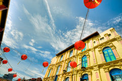 Chinatown at Noon. Red lanterns strung above the narrow lanes in Chinatown, Singapore, as seen against the sky at noon stock photo