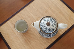 Chinaware blue and white porcelain teapot and empty cup on bamboo tablemat.  Stock Photos