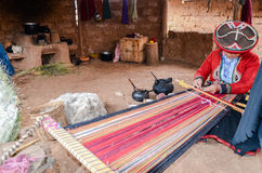 CHINCHERO, PERU- JUNE 3, 2013: Native Cusquena woman dressed in traditional colorful clothing works on a loom outside her house Stock Photos